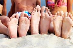 Getaway. Soles of teenagers sunbathing on sandy beach Royalty Free Stock Photos