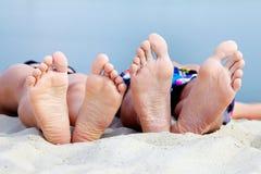 Getaway. Soles of teenagers sunbathing on sandy beach Stock Image
