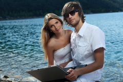 Getaway with computer. Happy young couple sitting together near the sea with a laptop Royalty Free Stock Photo