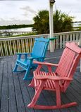 Getaway. Rocking chairs in color on the deck overlooking the waterway Royalty Free Stock Photos