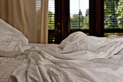 Getaway Room. Scatter bed sheets on a comfortable bed Stock Photo