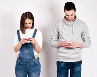 Geteilte junge Paare beschäftigt mit ihren Smartphones jeder Stockfoto