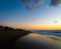 Geteilter Strand zwischen Meer und Gebäude mit schönem Sonnenaufgang Stockbilder