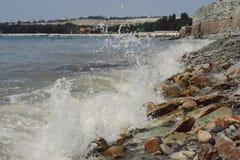 Getijde droeg De golven slaan tegen stenen stock foto