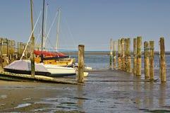 Getijdehaven met zeilboten en meertrosposten at low tide royalty-vrije stock foto
