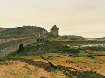 Getijden in het meer in Eilean Donan Castle, Schotland De populaire steenachtige brug royalty-vrije stock fotografie