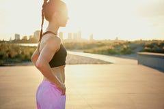 Getonte geeignete junge Frau hintergrundbeleuchtet durch den Sonnenaufgang Stockfotos