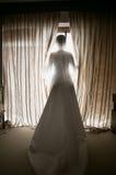 Getonter Schuss der eleganten Braut Fenster Hotel heraus betrachtend Lizenzfreies Stockfoto