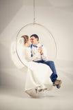Getonter Schuss der glücklichen Braut und des Bräutigams, die in Plastikschwingen cha sitzt Stockfotografie