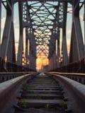 Getontes Bild der Eisenbahn mit Lagerschwellen und der Bahnbrücke auf einem Hintergrund des mehrfarbigen Sonnenuntergangs lizenzfreie stockfotografie