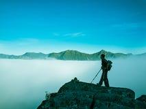 Getontes Bild einer erwachsenen Frau, die auf einen Berg mit einem Rucksack und Alpenstöcke gegen Berge in einem Nebel steht Lizenzfreie Stockbilder