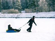 Getontes Bild einer glücklichen Familie, in der die Mutter einen kleinen Jungen auf einem Schlitten im Schnee trägt Lizenzfreies Stockbild