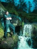 Getontes Bild eines erwachsenen Mannes in der Strickjacke, die nahe einem Nebenfluss auf dem Hintergrund von Felsen steht Stockbilder