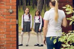 Getontes Bild von zwei Schulmädchen, die zur Schule am Morgen verlassen Lizenzfreie Stockfotos