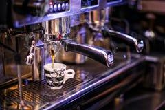Getontes Foto, das Tasse Kaffee mit Kaffeemaschine, Hintergrund für Kaffeestube vorbereitet Lizenzfreie Stockbilder