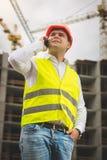 Getontes Porträt des jungen männlichen Ingenieurs, der telefonisch spricht und im Bau errichtend betrachtet stockbild