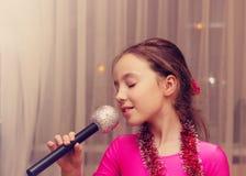 Getontes Porträt des netten kleinen Mädchens, das in ein Mikrofon singt Lizenzfreie Stockfotografie