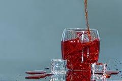 Getränk, das in Glas-w-/icewürfel gießt Lizenzfreies Stockbild