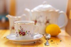 Getränk-, Entspannungs- und Teepartykonzept - Teesatz der Schale, des Topfes, des Löffels, der Zitrone und der Untertasse Stockbild