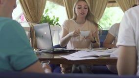 Getränkkaffee des jungen Mädchens und Unterhaltung am Telefon beim Studieren im Café mit Freunden stock video