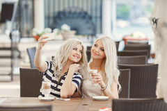 Getränkkaffee mit zwei Mädchen und benutzen das Telefon Stockfotografie