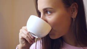 Getränkmorgenkaffee der jungen Frau schaut im Fenster stock video