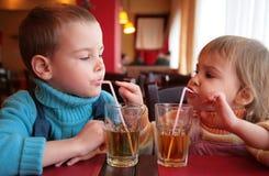 Getränksaft des kleinen Jungen und des Mädchens Stockfotos