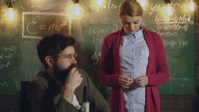 Geträumter Lehrer und Studentin nahe bei Rückenbrett, auf dem Formeln geschrieben werden Professor nimmt eine Matheprüfung profes stock video footage