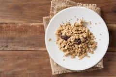 Getreide in der weißen Platte auf hölzernem Hintergrund Stockfotografie