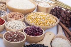 Getreidekörner, Samen, Bohnen auf hölzernem Hintergrund Stockbild