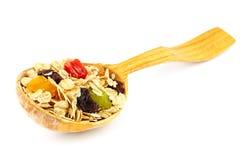 Getreidemuesli oder -hafer blättert mit Trockenfrüchten auf dem hölzernen lokalisierten Löffelstudio ab Lizenzfreie Stockfotografie