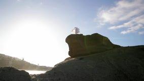 Getrennt auf Schwarzem Frauen im weißen Kleid und mit dem Schal, der auf dem Felsen steht tanzen flugwesen bewegen stock video