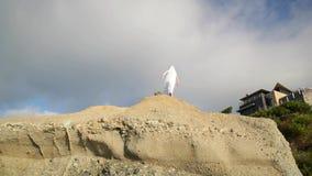 Getrennt auf Schwarzem Frauen im weißen Kleid und mit dem Schal, der auf dem Felsen steht tanzen flugwesen bewegen stock video footage