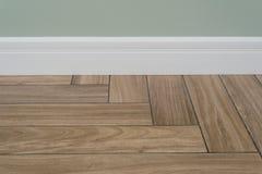 Getrennt auf Weiß Helle Mattwand, weiße Fußleiste und Fliesen, die Hartholzbodenbelag nachahmen Lizenzfreies Stockfoto