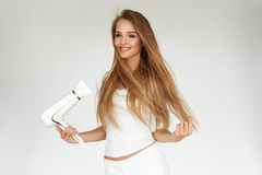 Getrennt auf weißem Hintergrund mit Ausschnittspfad Frau, die schönes blondes langes gerades Haar trocknet Lizenzfreies Stockbild
