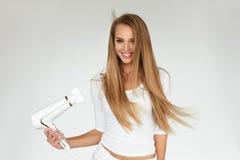 Getrennt auf weißem Hintergrund mit Ausschnittspfad Frau, die schönes blondes langes gerades Haar trocknet Lizenzfreie Stockfotos