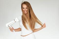 Getrennt auf weißem Hintergrund mit Ausschnittspfad Frau, die schönes blondes langes gerades Haar trocknet Lizenzfreie Stockbilder