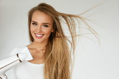 Getrennt auf weißem Hintergrund mit Ausschnittspfad Frau, die schönes blondes langes gerades Haar trocknet Lizenzfreies Stockfoto