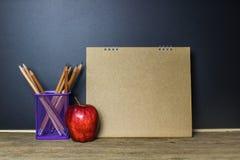 getrennte alte Bücher Bleistift und roter Apfel auf hölzerner Tabelle Lizenzfreies Stockfoto