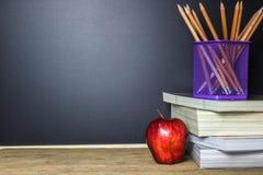 getrennte alte Bücher Bleistift und roter Apfel auf hölzerner Tabelle Lizenzfreie Stockfotos