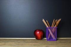 getrennte alte Bücher Bleistift und roter Apfel auf hölzerner Tabelle Stockfoto