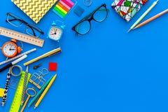 getrennte alte Bücher Briefpapier für Schulschülermodell mit Gläsern und Notizbuch auf Draufsicht des blauen Hintergrundes kopier Stockfotos