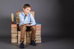 getrennte alte Bücher Ein Junge sitzt auf einem Thron von Büchern Stockfoto