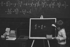 getrennte alte Bücher Kleiner Junge, der Gleichung auf Tafel löst Vorschultraining für intelligentes Kind Stockfotografie