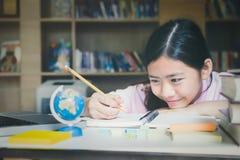 getrennte alte Bücher Mädchenlesung und -schreiben in der Bibliothek Lizenzfreie Stockfotografie