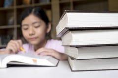 getrennte alte Bücher Mädchenlesung und -schreiben in der Bibliothek der Schule Stockbild