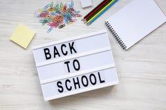 getrennte alte Bücher ` Zurück zu Schule-` Wort auf lightbox, Zubehör für Studie über weißem hölzernem Hintergrund, Draufsicht Stockfoto