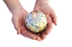Getrennte Erdekugel in den Händen der alten Frau Stockbilder