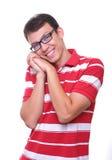 Getrennter netter junger Mann, der mit Gläsern lächelt Lizenzfreies Stockfoto