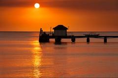 Getrennter Pier mit orange Tonsonnenuntergang Lizenzfreie Stockfotos